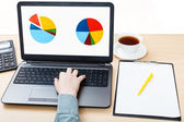 Laptop with chart on screen on office desk — Stock Photo