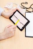 Doctor checks patient electrocardiogram — Stock Photo