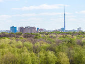 Modern city and green woods in spring — Stock Photo
