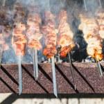 Many shish kebab sticks preparing on grill — Stock Photo #78018188