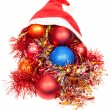 Christmas decorations fall out from red santa hat — Stock Photo #78073382