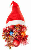 Christmas decorations spill over red santa hat — Stock Photo
