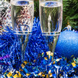 Two glasses with blue Xmas decorations and tree 1 — Stock Photo #78295890