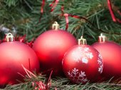 Four red Christmas baubles on Xmas tree background — Stock Photo