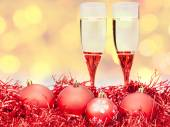 Glasses, red Xmass baubles on blurry background — Stock Photo
