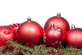 Red Christmas balls on green spruce branch — Stock Photo