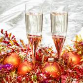 Glasses of sparkling wine with gold Xmas baubles — Stock Photo
