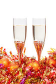 Two glasses of champagne and gold Christmas bauble — Stock Photo