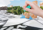 Hand deletes ice floe near waterfront by eraser — Stock Photo
