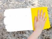 Hand deletes frozen pattern on glass by yellow rag — Stock Photo
