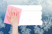 Hand deletes winter snowflake on window by pink rag — Stock Photo