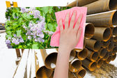 Hand deletes industrial landscape by pink cloth — Stock Photo