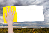 Hand deletes rainy clouds over town by yellow rag — Stock Photo