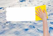 Hand deletes snow surface by yellow rag — Stock Photo