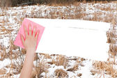 Hand deletes frozen swamp by pink rag — Stock Photo