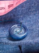 Attaching of button to blue silk suit by needle — Stock Photo