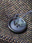 Attaching of button to green tweed by needle — Stock Photo