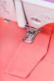 Attaching pocket to red shirt on sewing machine — Stock Photo