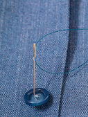 Attaching of button to blue silk dress by needle — Stock Photo