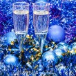 Sparkling wine glasses in blue Xmas decorations — Stock Photo #82433028