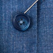 Attaching of button to blue silk cloth by needle — Stock Photo