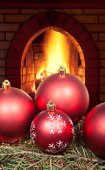 Red Christmas balls on spruce tree and fireplace — Stock Photo