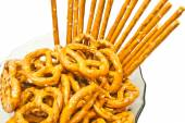 Tasty salted pretzels and breadsticks on a plate — Stockfoto