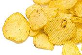 Many corrugated potato chips on white — Stock Photo