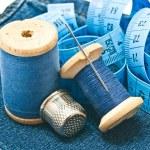 Thimble, meter and spools of thread on denim — Stock Photo #66014653
