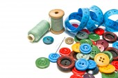 Plastic buttons and spools of thread — Stock Photo
