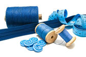Blue buttons, zipper and spools of thread — Stock Photo