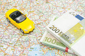 Money and yellow car on map  — Stock Photo