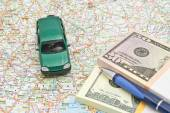 Money, pen and green car on map — Stock Photo