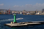 Green lighthouse in the port — Stock Photo