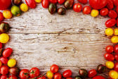 Frame of tomatoes family varieties over a  wooden background — Stock Photo