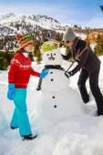 Winter fun, happy family playing with snowman — 图库照片