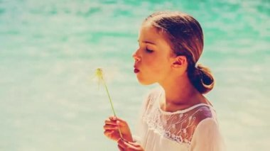 Summer joy, young girl blowing dandelion on the beach — Stock Video