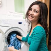 Putting a cloth into washing machine — Stockfoto