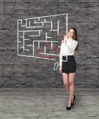 Beautiful businesswoman showing something in  maze — Stock Photo