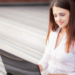 Portrait of a smiling young woman using laptop on outdoors — Stock Photo #53001515