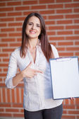 Smiling young elegant businesswoman with clipboard standing in a — Stock fotografie