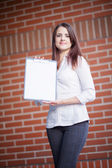 Business woman showing blank clipboard at her office  — Foto Stock