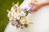 Beautiful wedding flowers in hands — Stock Photo