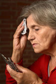 Sick aged woman calling doctor — Stock Photo