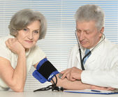 Elderly doctor measuring blood pressure — Stock Photo