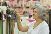 улыбаясь старая дама в магазине — Стоковое фото