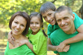 Cheerful family in green shirts — Stock Photo