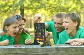 Happy family in green shirts playing — Stock Photo