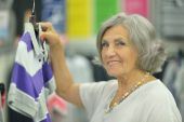 Smiling old lady in store — Stock Photo