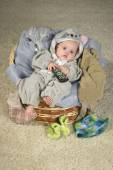 Baby girl in the basket with TV remote — Stock Photo